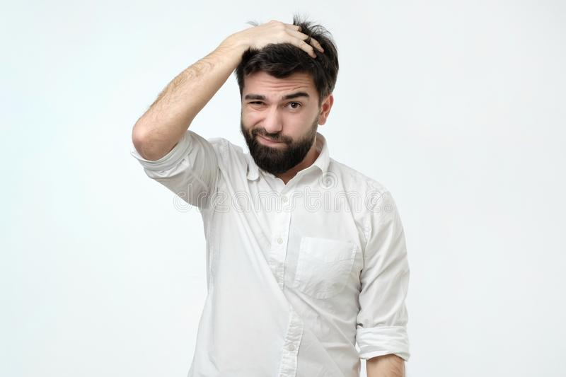 Hispanic man with beard looking with puzzled expression, scratching head, being clueless royalty free stock photos