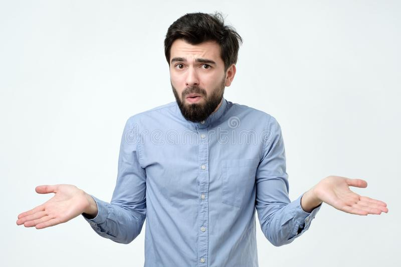 Hispanic man in blue shirt throws up his hands in disbelief. Like saying I am not sure now royalty free stock image