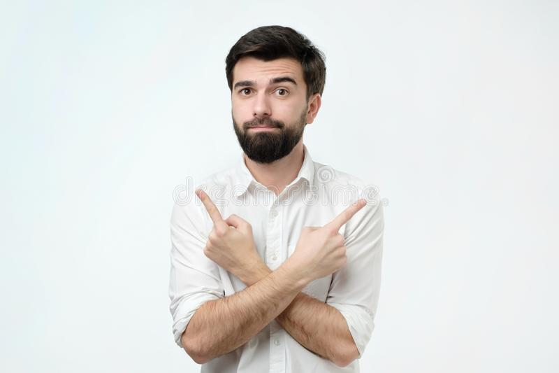Hispanic man choosing between two options concept. He points to different sides by his fingers. Young hispanic man choosing between two options concept. He royalty free stock photo