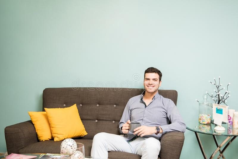 Hispanic man drinking tea in a waiting room stock photography