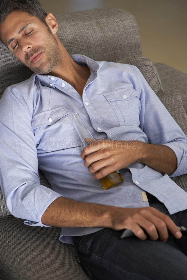 Hispanic Man Fallen Asleep On Sofa Watching TV stock photography