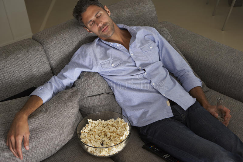 Hispanic Man Fallen Asleep On Sofa Watching TV royalty free stock photo