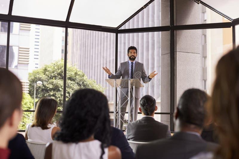 Hispanic man gesturing to audience at business seminar stock image