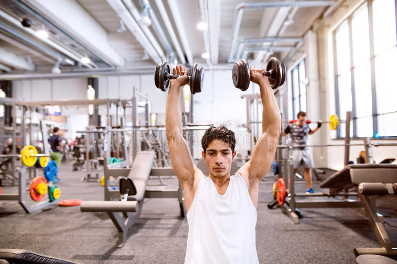 Hispanic man in gym sitting on bench, working out with weights stock image