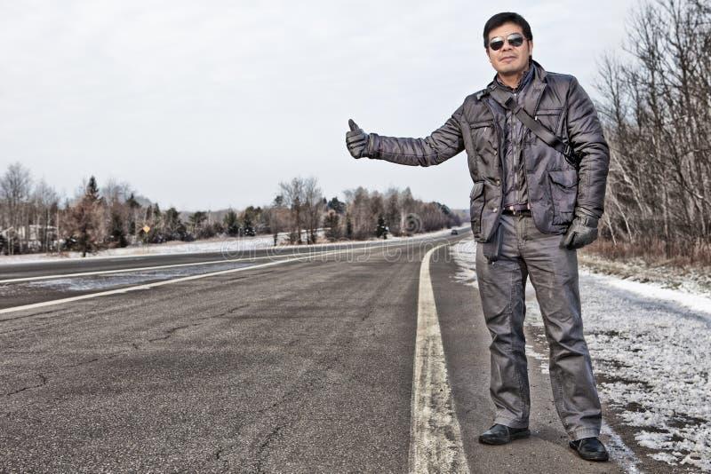Hispanic man hitchhiking in Canada stock photos