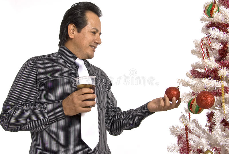 Hispanic Man Looking At A Decorated Christmas Tree Royalty Free Stock Images