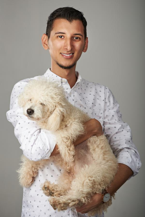 Hispanic man with poodle dog. Hispanic young smiling man with poodle dog royalty free stock images