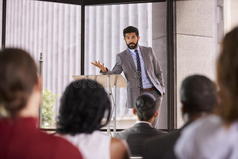 Hispanic man presenting business seminar leaning on lectern stock photography