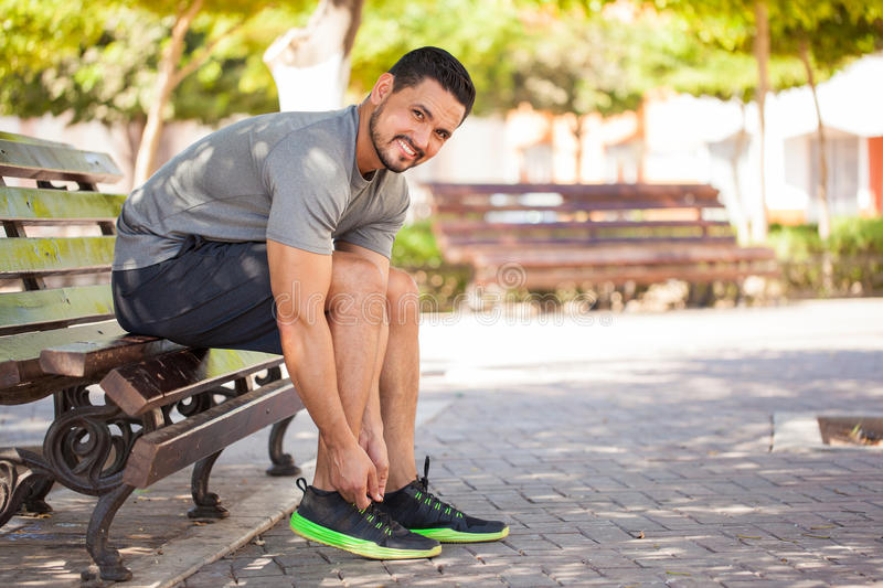 Hispanic man ready to go for a run. Portrait of a handsome Hispanic young man getting ready to go running at a park and smiling stock photography
