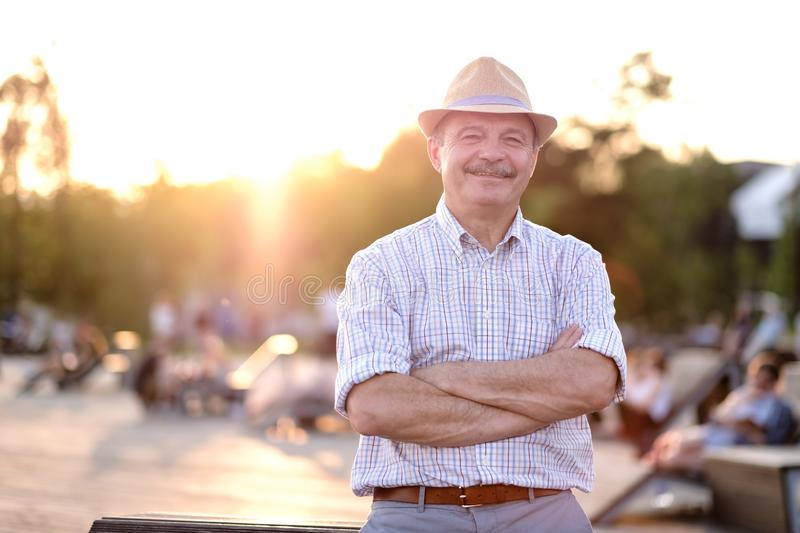 Hispanic man in summer hat with folded hands smiling looking at camera standing on city park. Happy mature hispanic man in summer hat with folded hands smiling royalty free stock photos