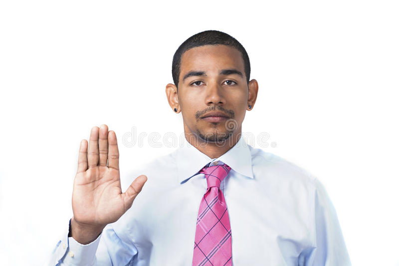 Hispanic man taking oath. Hispanic man taking an oath or pledge with right hand raised and serious expression royalty free stock photo