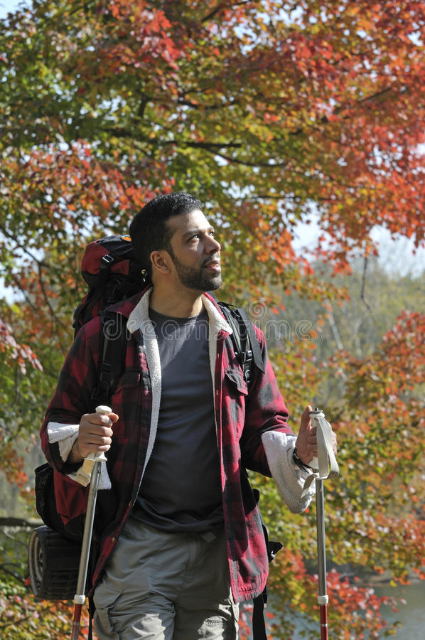 Hispanic Man with Trekking Poles and Backpack stock photo