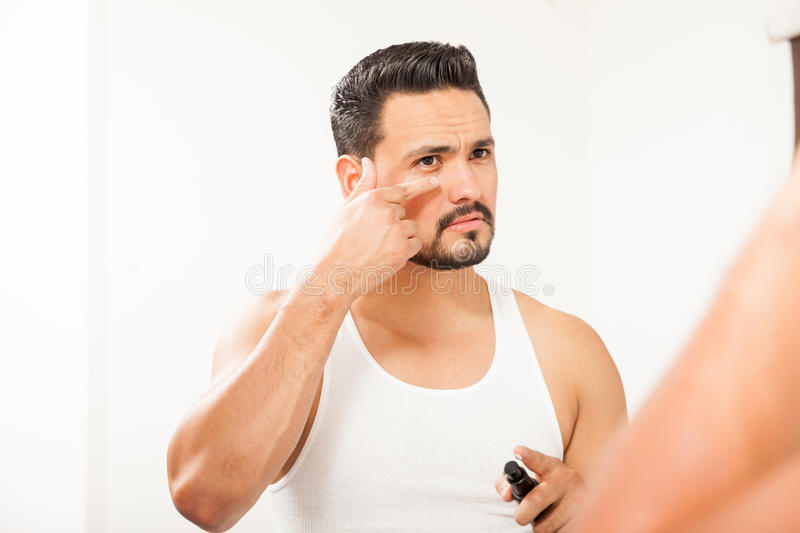 Hispanic man using an under eye cream. Good looking Hispanic young man putting on some anti-aging cream to prevent bags under eyes in the bathroom royalty free stock photo