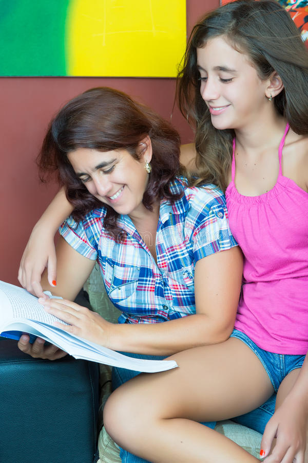 Hispanic mother and her pretty daughter reading stock images