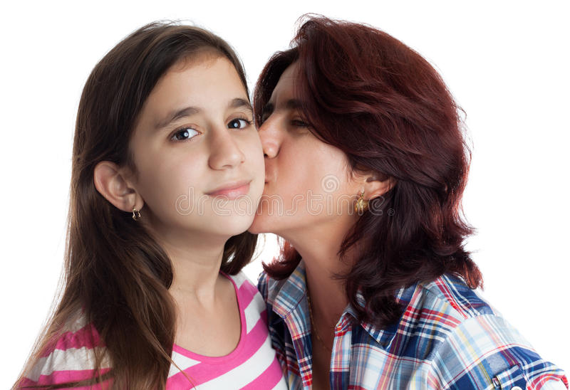 Hispanic mother kissing her beautiful daughter. Isolated on white stock image