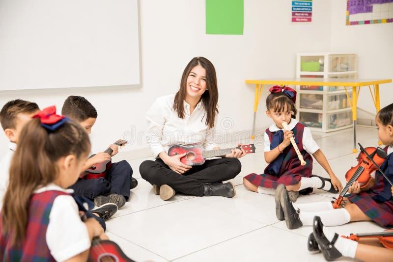 Hispanic music teacher in a preschool classroom stock images