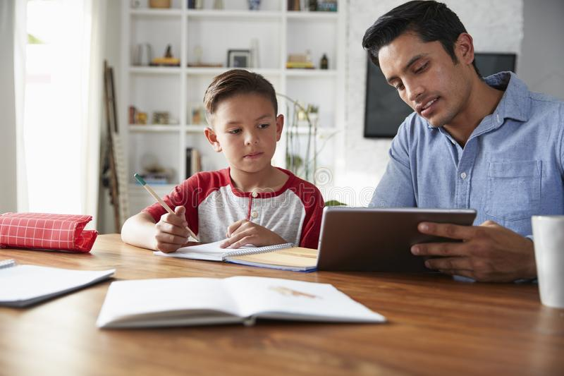 Hispanic pre-teen boy sitting at table working with his home school tutor, using tablet computer stock photography