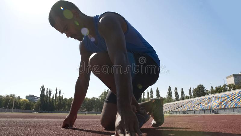 Hispanic runner in starting position to run on track, goal achievement in sport royalty free stock photo