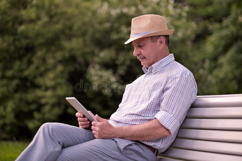 Hispanic senior man in summer hat reading tablet in park copy space. Hispanic senior man in summer hat reading article on tablet in park copy space royalty free stock image