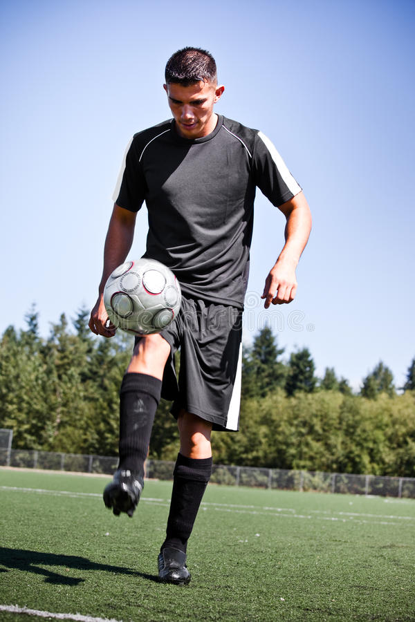 Download Hispanic Soccer Or Football Player Kicking A Ball Stock Photo - Image: 10968130