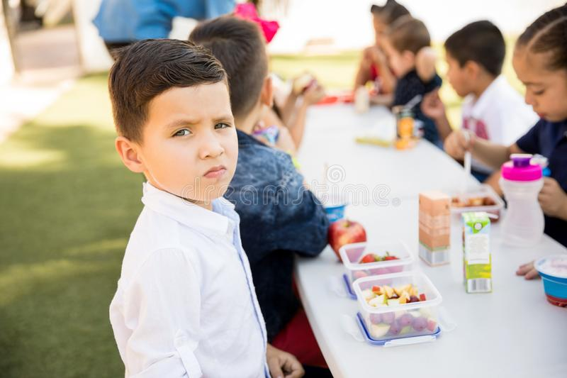 Hispanic student eating healthy. Portrait of a good looking Hispanic preschool student eating healthy food on his lunch break stock photo