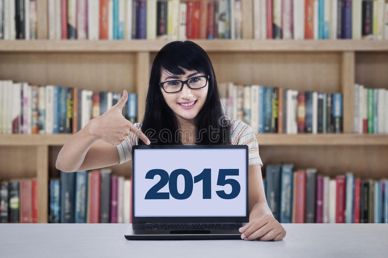 Hispanic student showing numbers 2015 on laptop. Beautiful female student sitting in the library and pointing at numbers 2015 on the laptop computer stock images