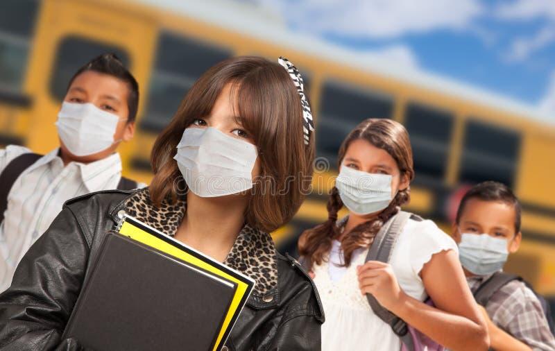 Hispanic Students Near School Bus Wearing Medical Face Face Masks stock photo