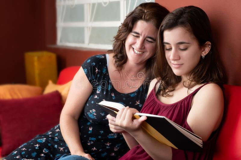 Hispanic teenage girl and her mom reading a book stock images