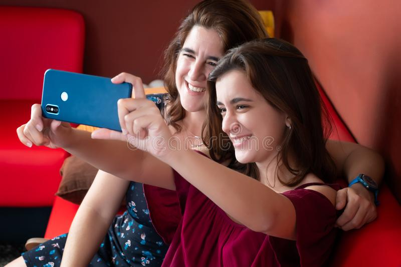 Hispanic teenage girl and her mother taking a selfie at home. Adult attractive beautiful camera care cellphone daughter family female friend friendship stock photography
