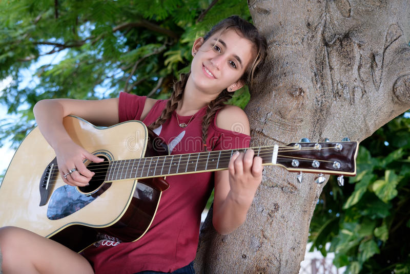 Hispanic teenage girl playing an acoustic guitar. Pretty hispanic teenage girl playing an acoustic guitar stock photos