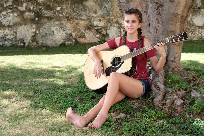 Hispanic teenage girl playing an acoustic guitar. Pretty hispanic teenage girl playing an acoustic guitar sitting on the grass royalty free stock image