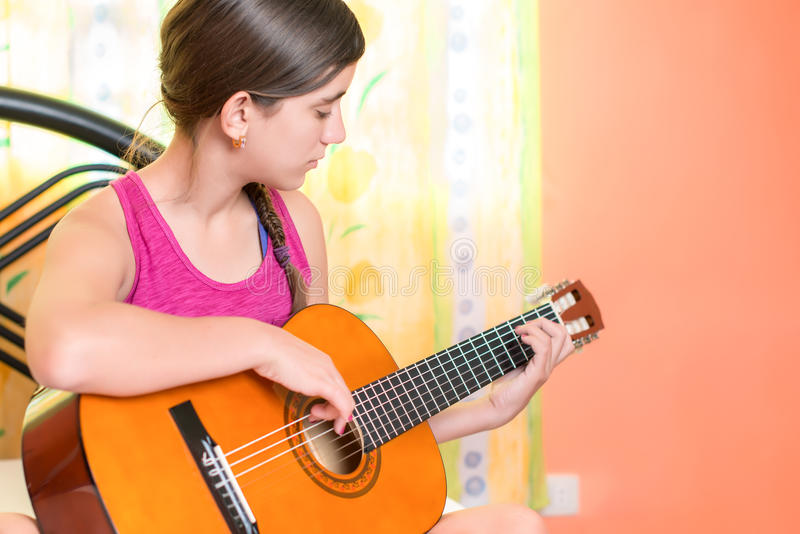 Hispanic teenage girl playing guitar at home stock image