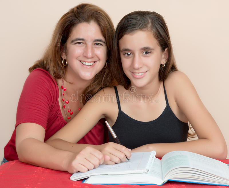Hispanic teenage girl studying with her mother stock image