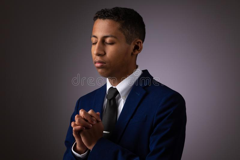 Hispanic Teenager Boy Seeking to Commune with God Via Prayer. Talking with God and Opening His Heart. On Gray Background stock images