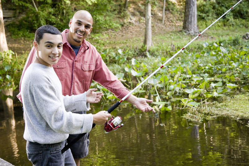 Hispanic teenager and father fishing in pond stock photo