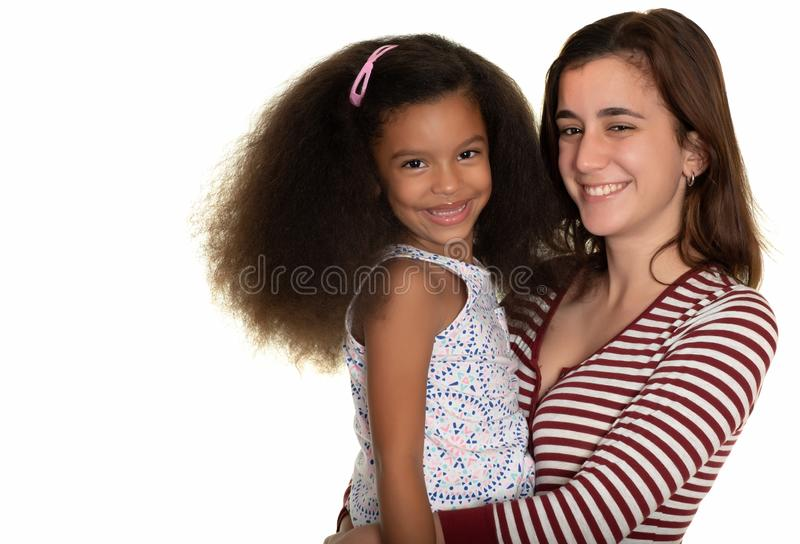 Hispanic teenager hugging an african american small girl. Isolated on white stock image
