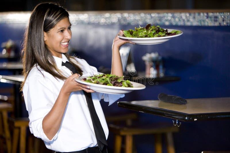 Hispanic waitress serving salads stock image