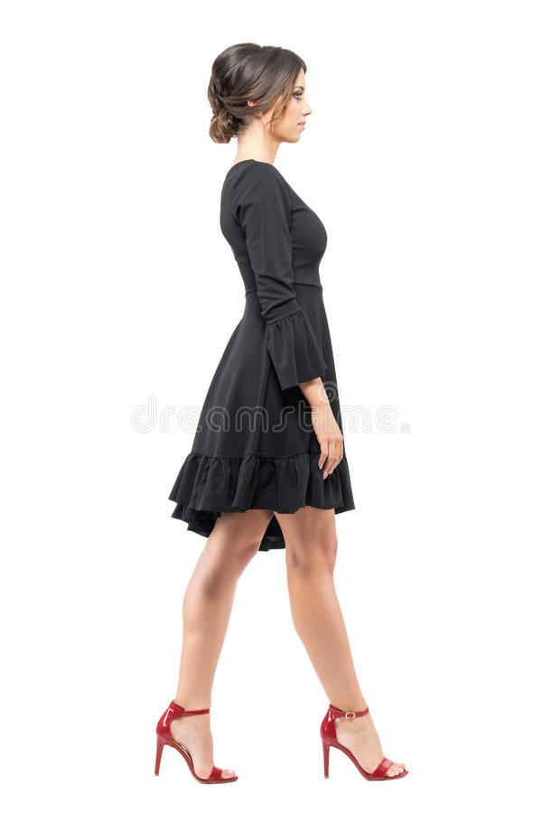 Hispanic woman in black dress and red high heels sandals walking looking ahead side view. Full body length portrait isolated on white background royalty free stock photos