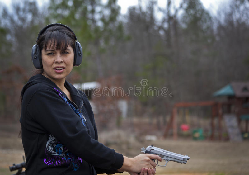 Hispanic Woman Firing Pistol Royalty Free Stock Image
