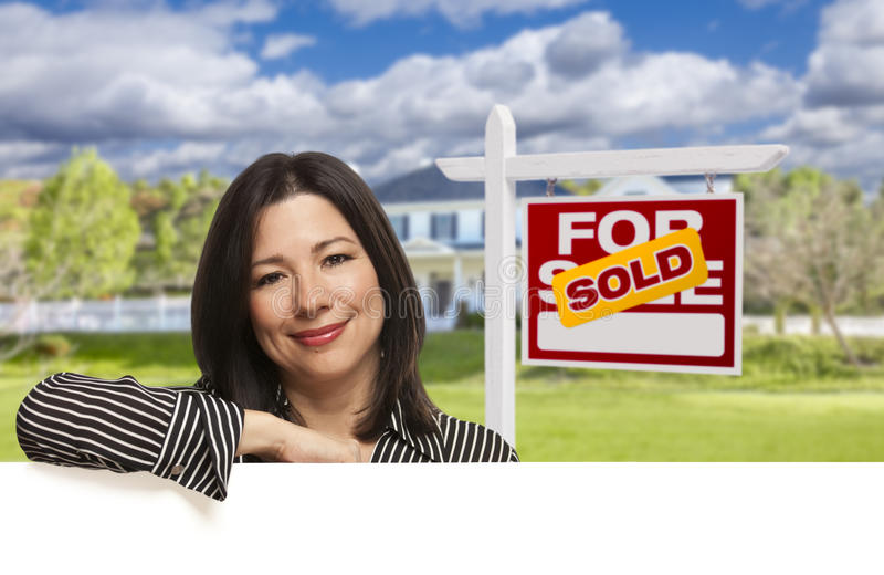 Hispanic Woman in Front of Sold For Sale Sign, House royalty free stock image