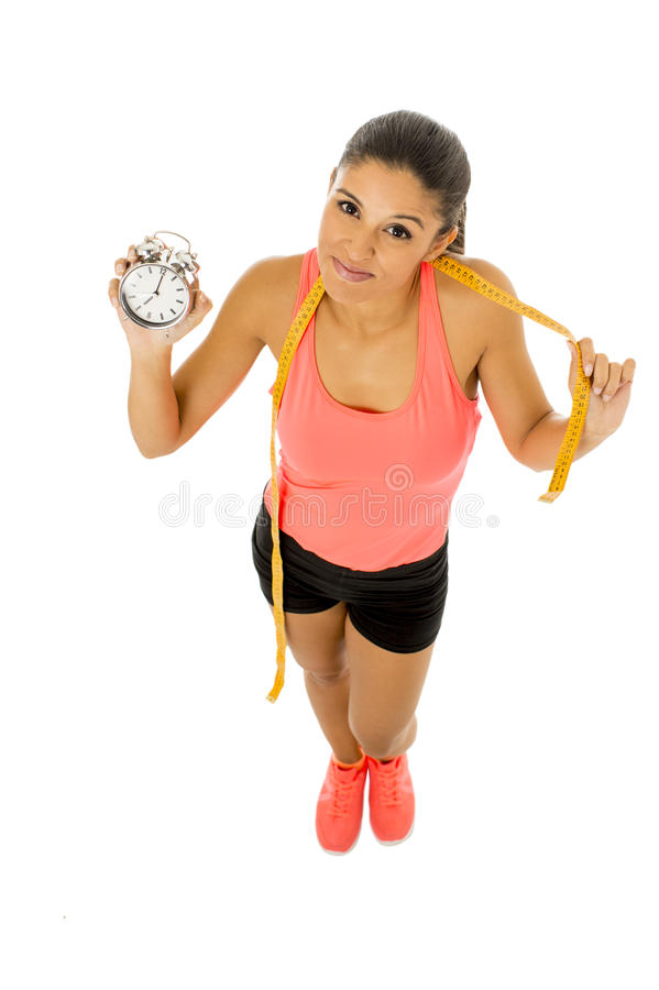 Hispanic woman holding alarm clock and taylor measure tape in time for sport and diet concept stock photography
