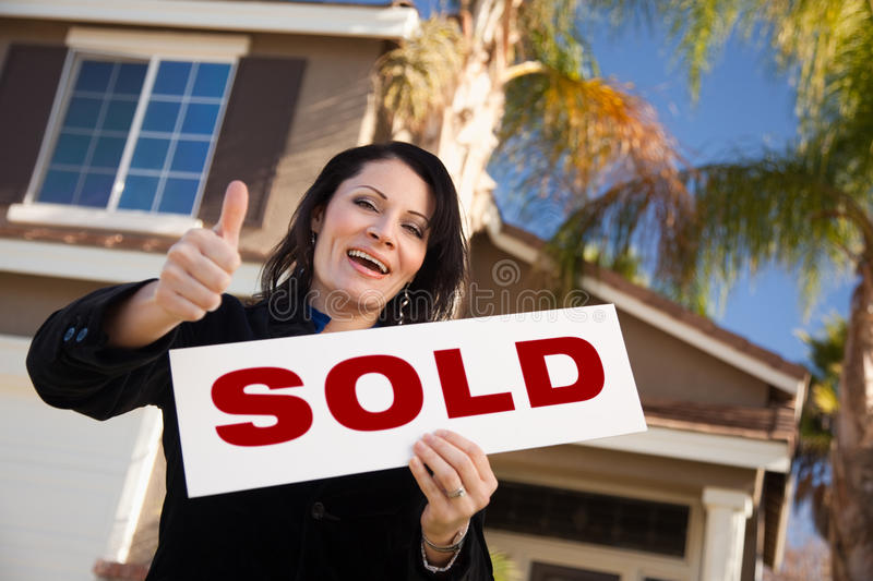 Hispanic Woman Holding Keys & Sold Sign royalty free stock photo