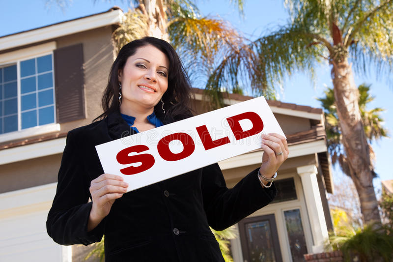Hispanic Woman Holding Sold Sign In Front of House. Happy Attractive Hispanic Woman Holding Sold Sign In Front of House stock images