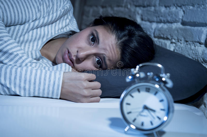 Hispanic woman at home bedroom lying in bed late at night trying to sleep suffering insomnia stock images