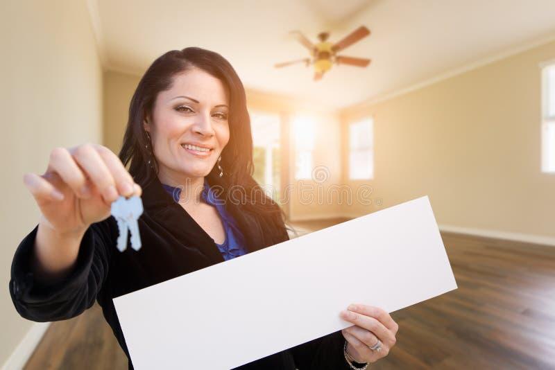 Hispanic Woman With House Keys and Blank Sign In Empty Room of House. Hispanic Woman With House Keys and Blank Sign In Empty Room of a New House stock photos