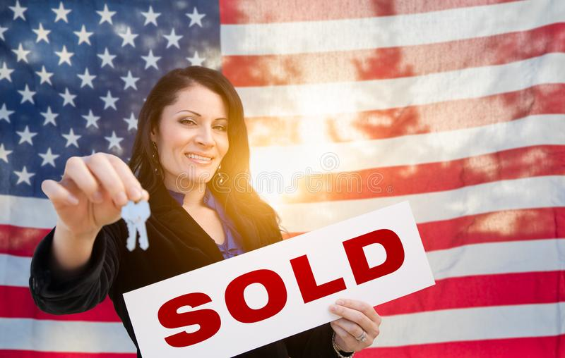Hispanic Woman House Keys and Sold Sign In Front of American Flag. Hispanic Woman House Keys and Sold Sign In Front of an American Flag royalty free stock photography