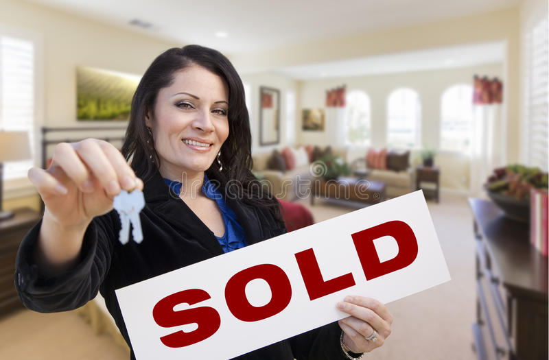 Hispanic Woman with Keys and Sold Sign in Living Room royalty free stock photos