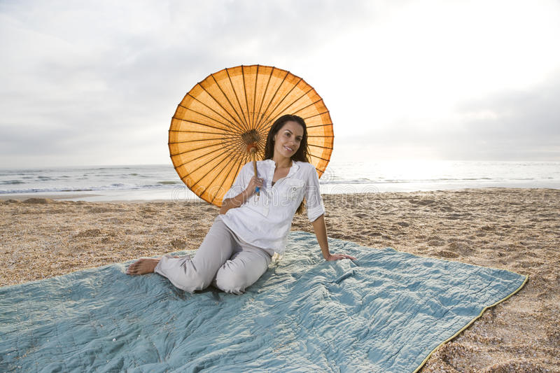 Download Hispanic Woman With Parasol On Beach Blanket Stock Photo - Image: 14769750