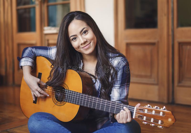 Hispanic woman paying acoustic guitar. Portrait of beautiful hispanic woman paying acoustic guitar indoors royalty free stock photo