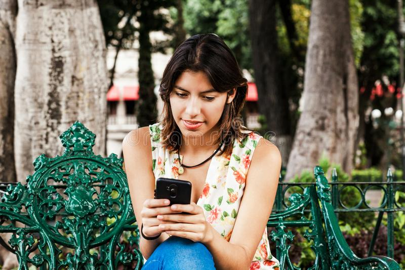 Hispanic woman texting with her phone, Mexican beautiful woman in Mexico stock photography